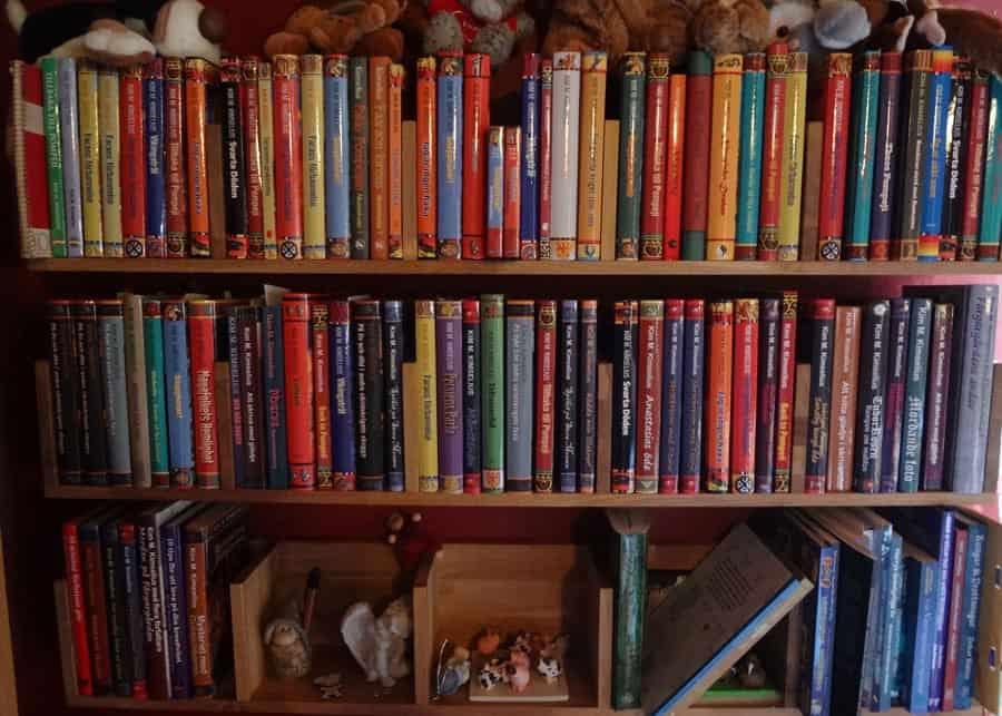 """""""Bilden är på hyllan med mina böcker, här finns alla utgåvor, utländska titlar och böcker jag har medverkat i. Snart får de sistnämnda flytta till en egen hylla, för det börjar bli trångt. Gosedjuren och prydnadssakerna är gåvor från mina fans"""", berättar Kim Kimselius."""